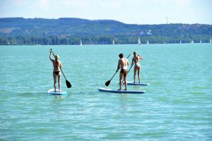 three people standing on paddle boards in blue clear water