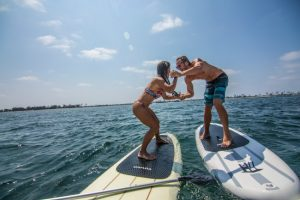 girl and a guy playing on paddle boards