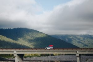 car on bridge with red kayak on roof