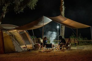 cooking dinner in the dark under a tent awning