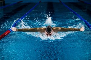 male swimmer doing butterfly with arms wide