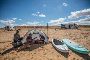 family on the beach with paddle boards next to the tent