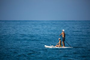 two people on a paddle board in the open blue water