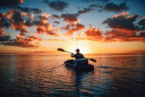 kayak fisherman paddling at sunrise